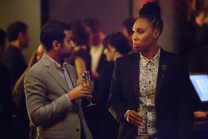 Dev and Denise in nice button-down shirts and blazers holding drinks at a bar, looking unamused at each other