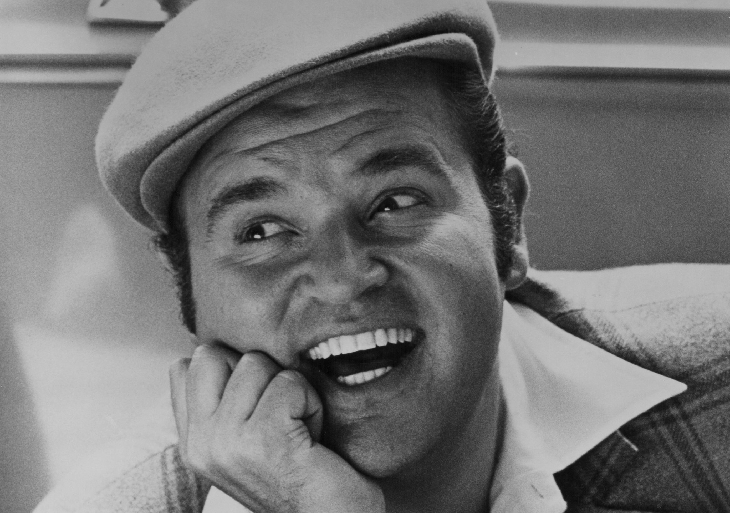 Black-and-white headshot-style photo of Dom DeLuise laughing
