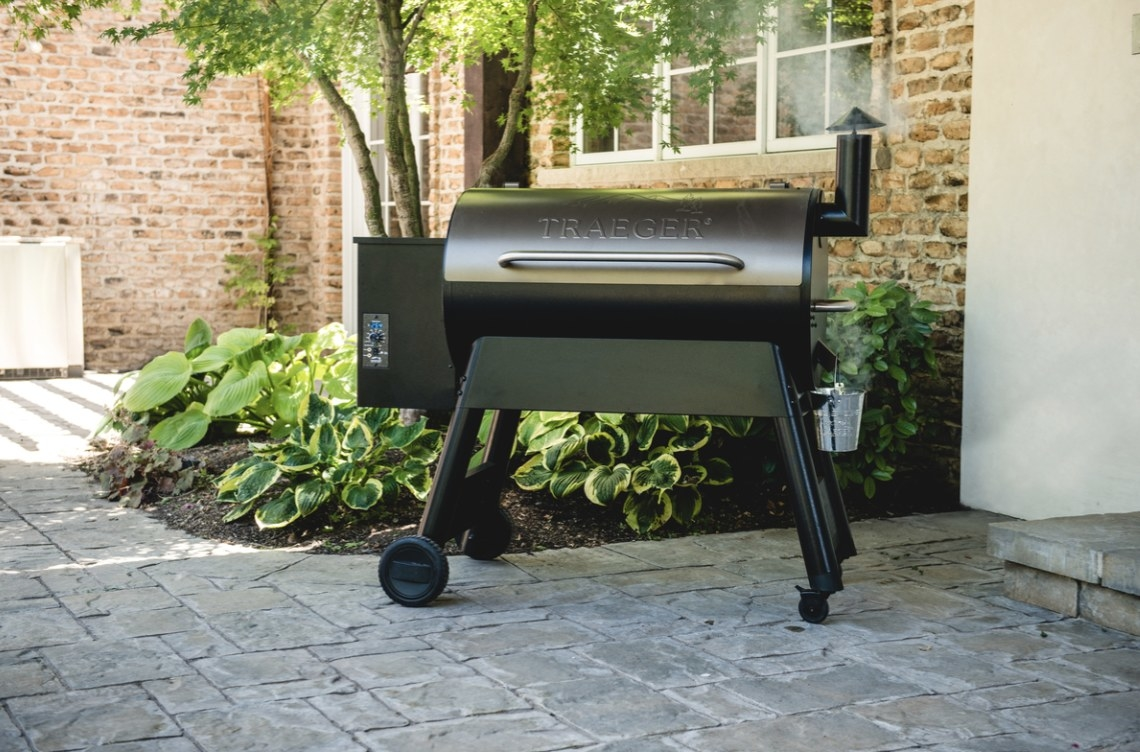 """The taupe oven says """"TRAEGER"""" has a black base/legs and is outside with smoke coming out from the top"""