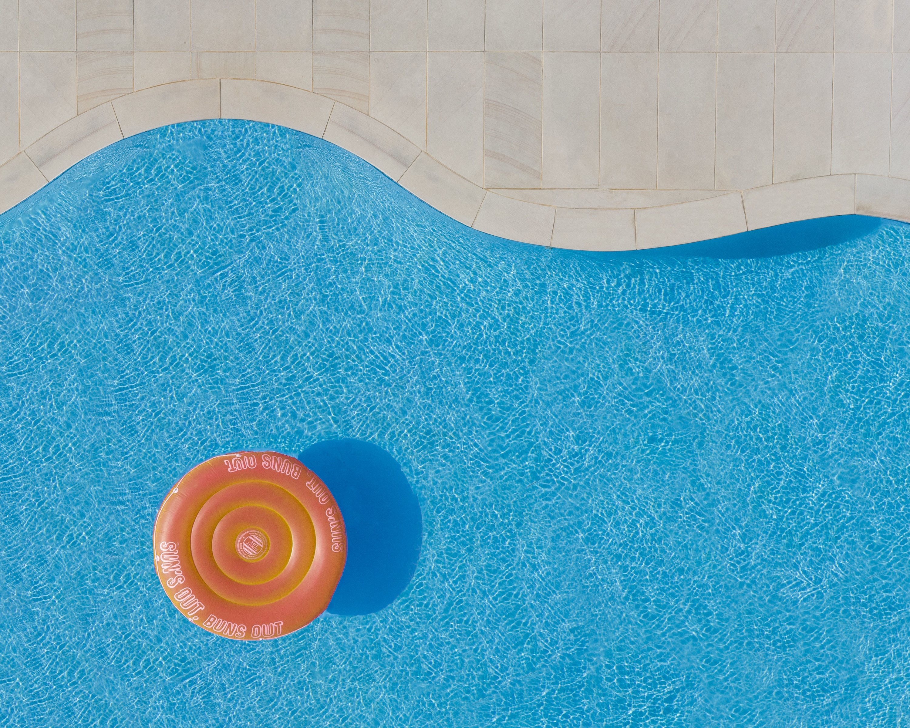 An overhead view of a doughnut shaped round floatie in a curved pool