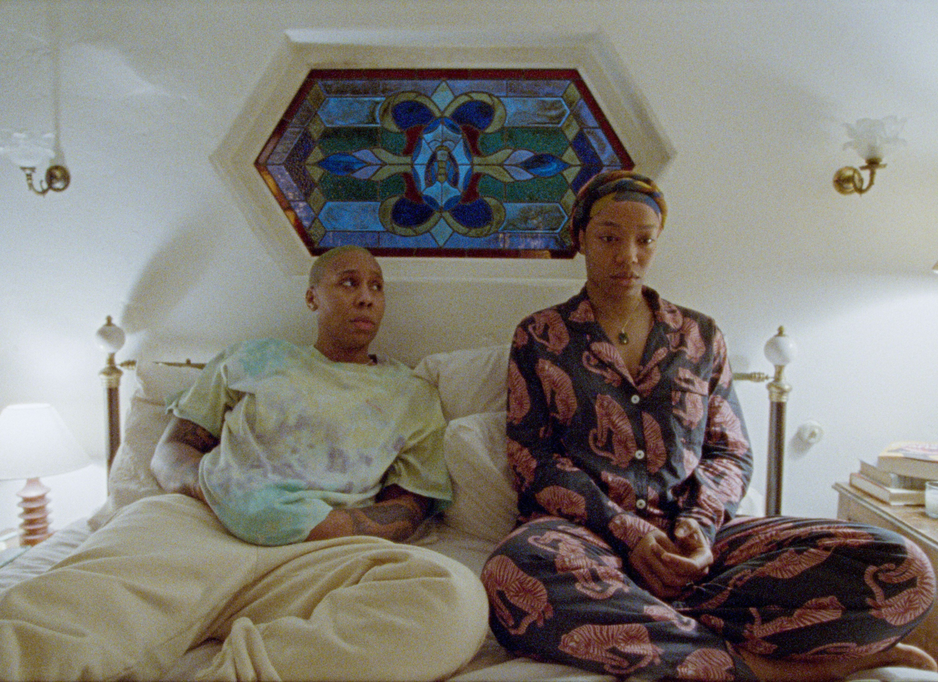 Denise in oversized tie-dyed shirt and sweats with Alicia in tiger pattern pajamas sitting in bed looking very concerned