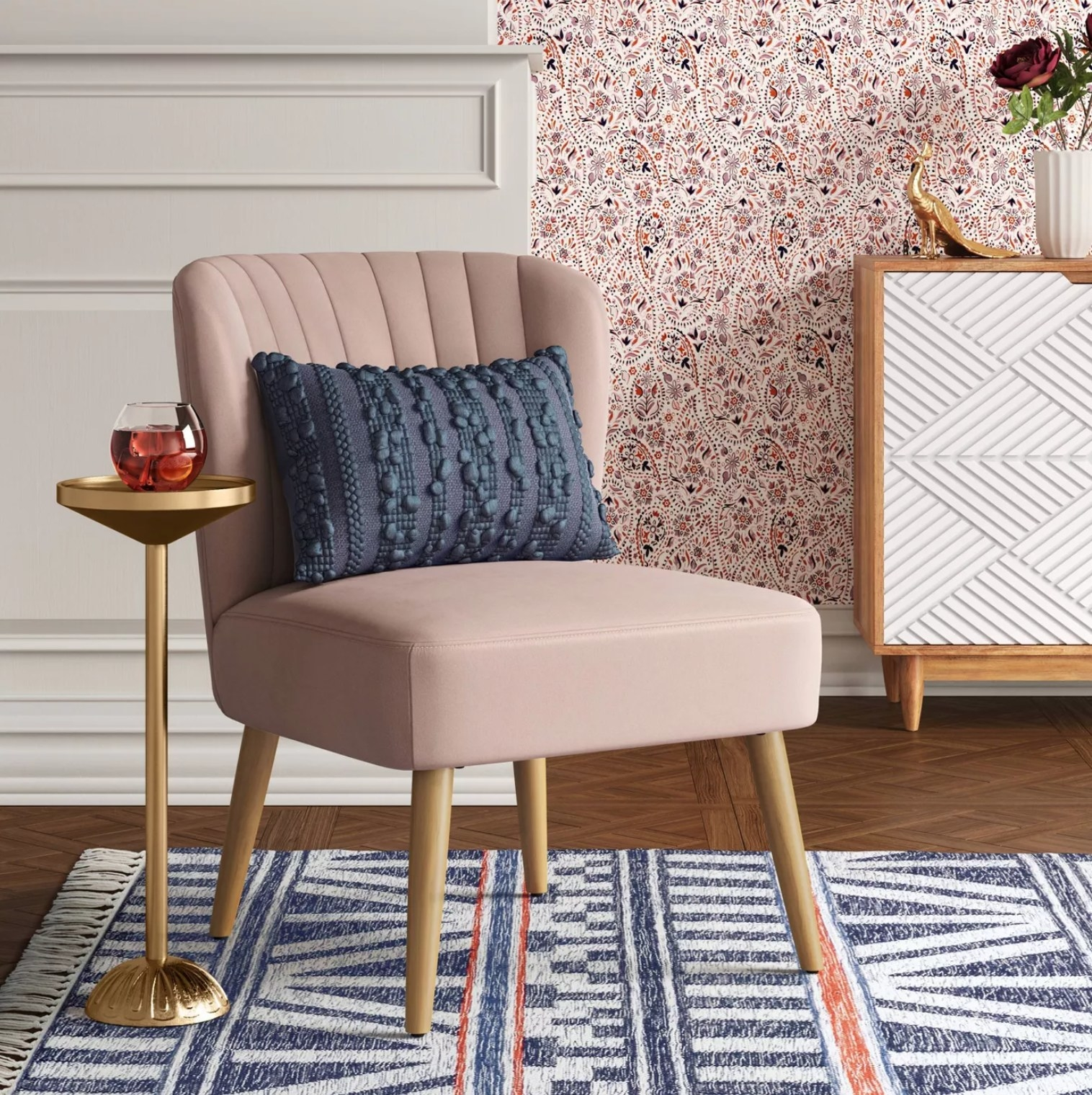 the pink chair with a blue pillow next to a gold side table with a drink on it