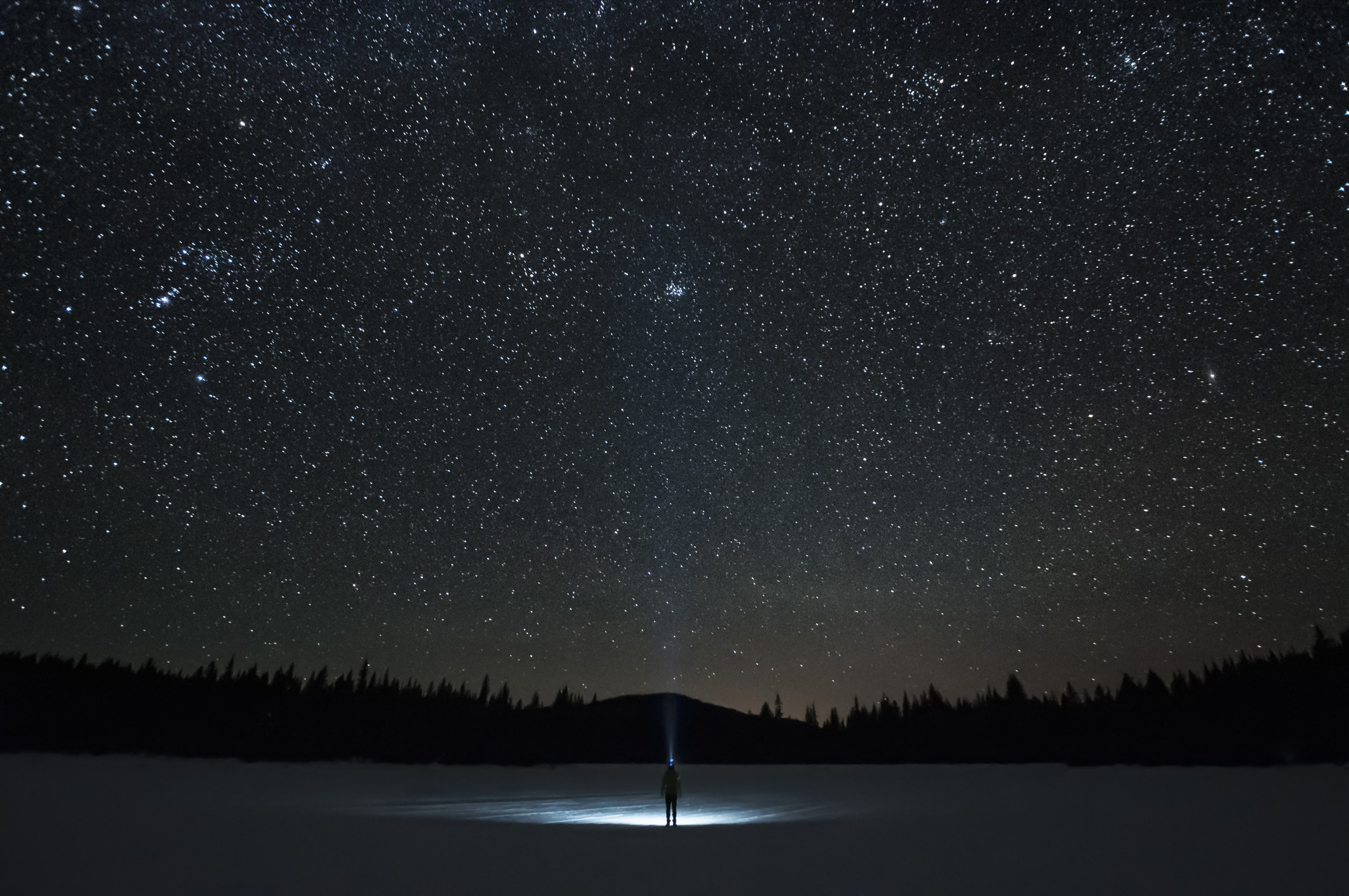 Man looking up at Pleiades star cluster and Orion constellation