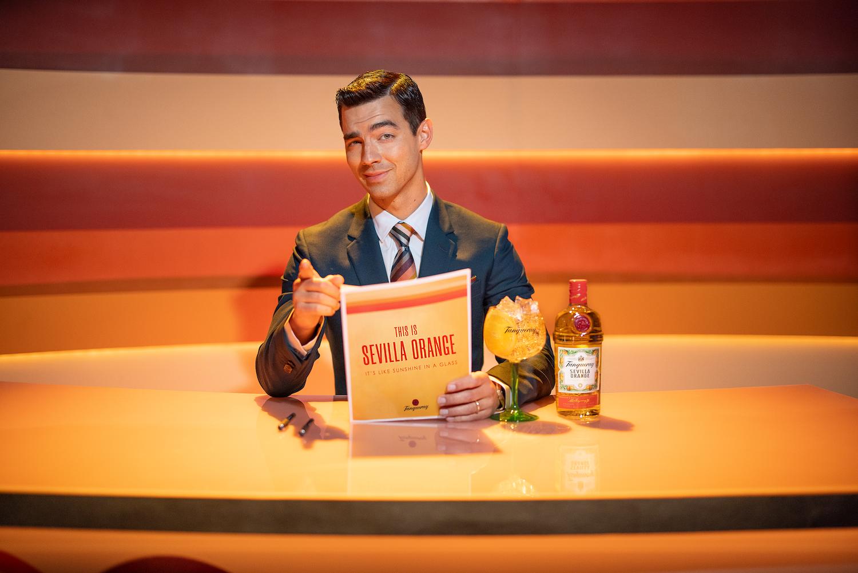 Joe Jonas sitting behind a desk in his content spot for Tanqueray Sevulla Orange
