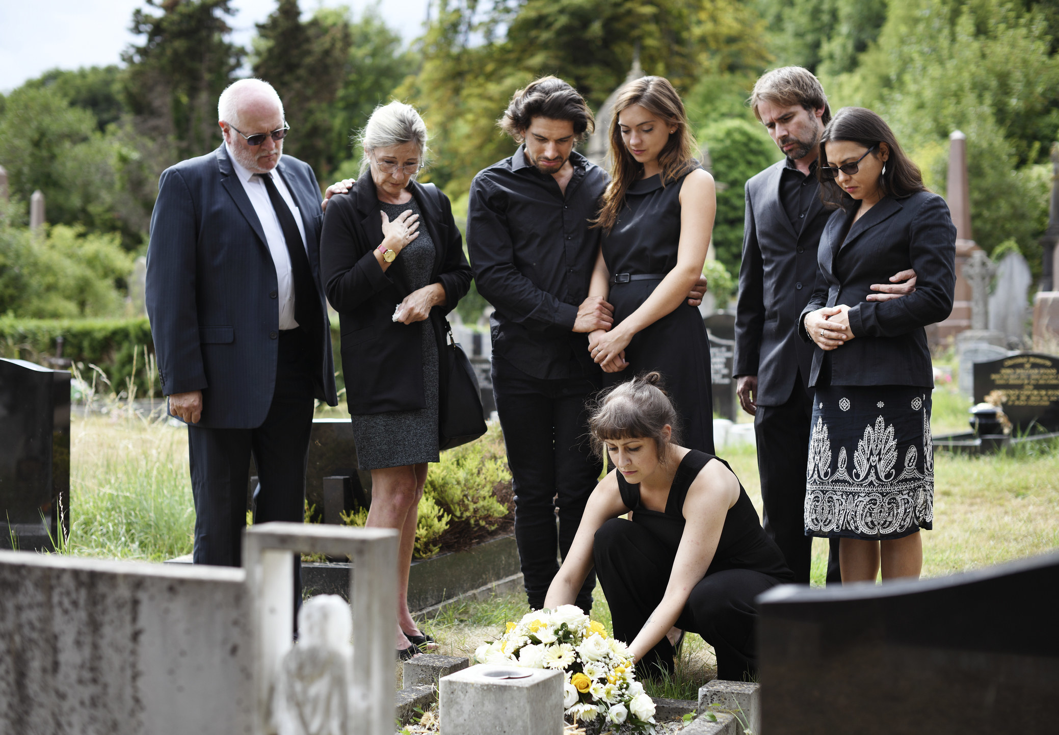 People laying flowers on a tombstone