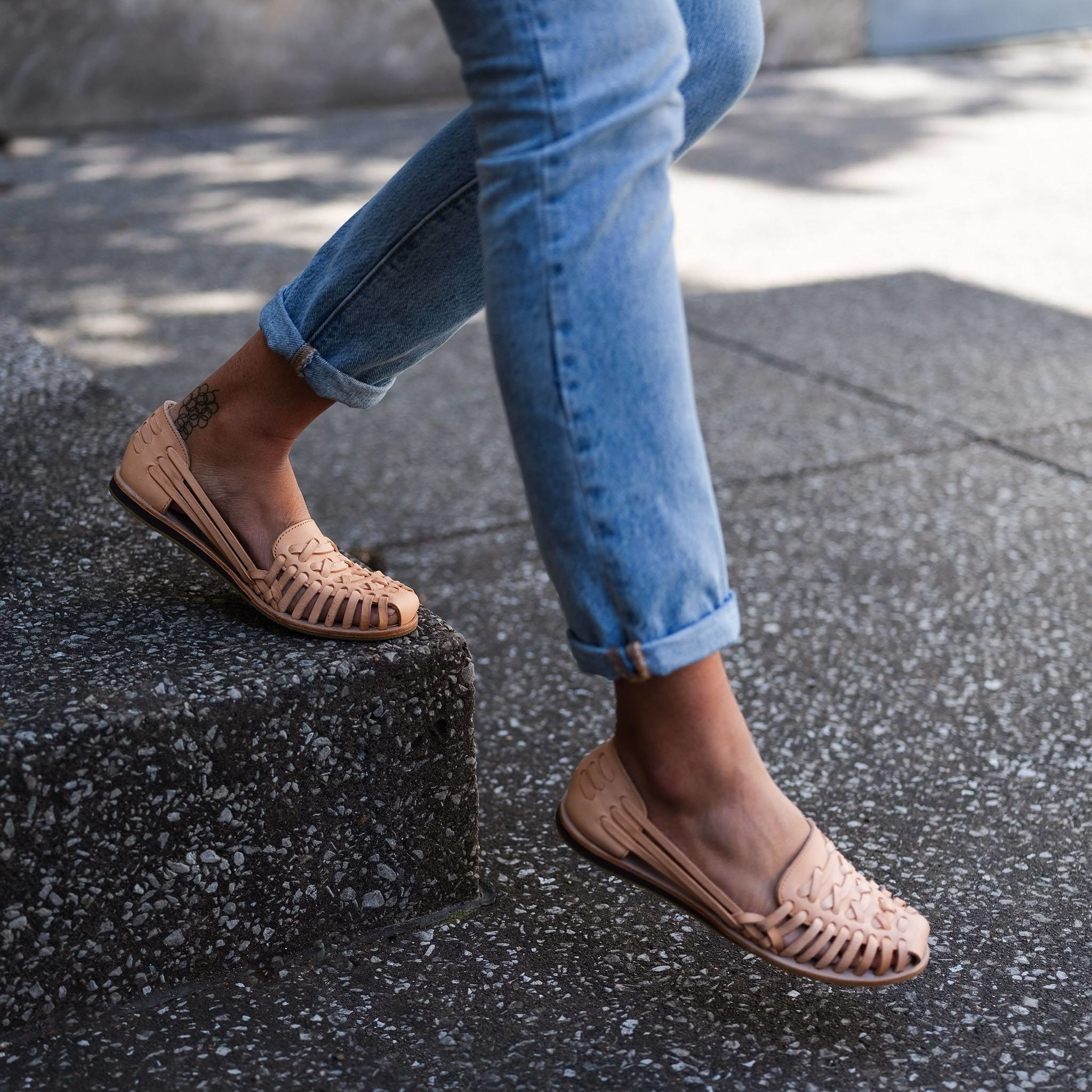Model wearing sandals while walking on sidewalk