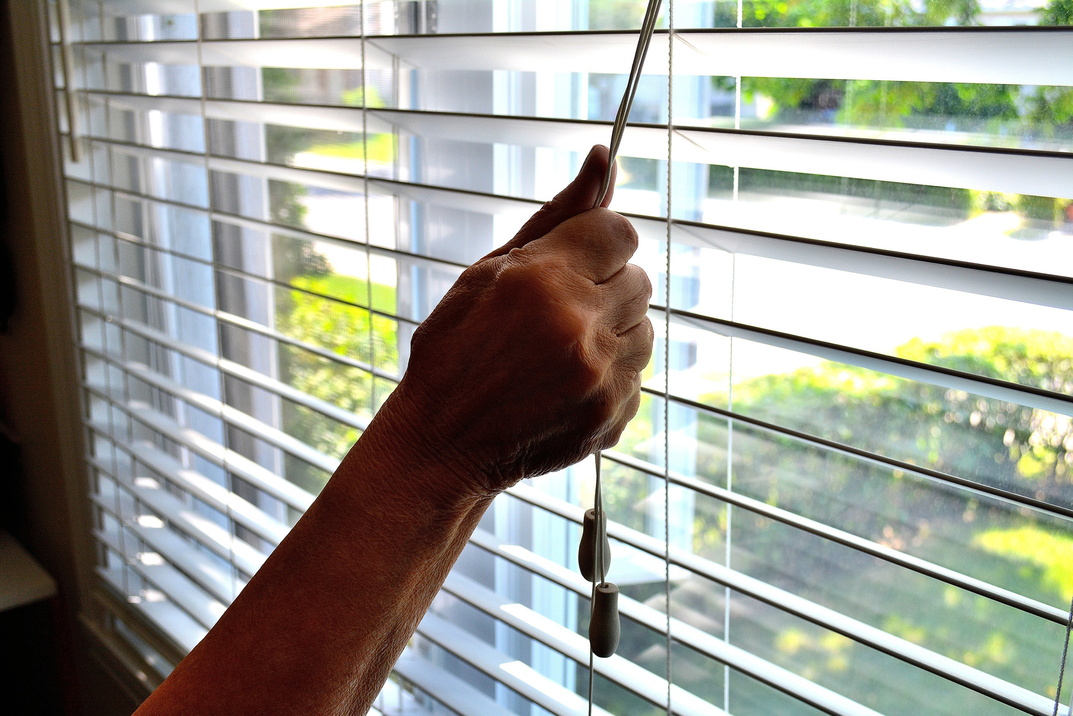 Person drawing the blinds on a bright day