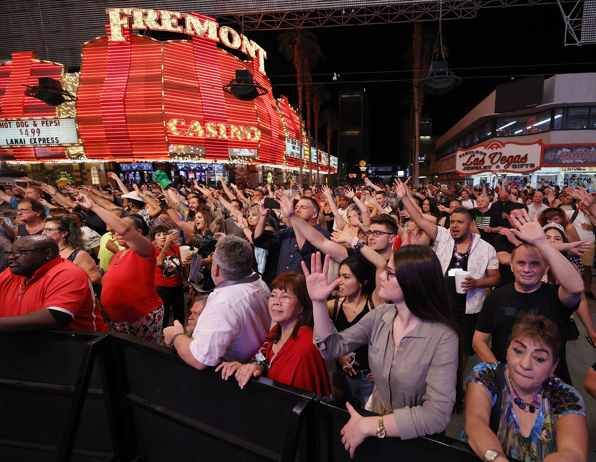 A crowd of people raise their hands as they watch a concert on a packed street in Las Vegas