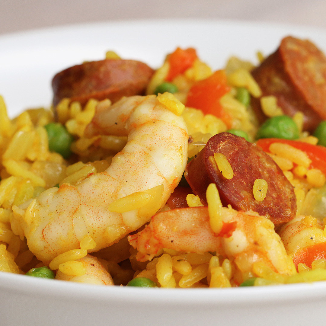 Yellow rice topped with sausage and prawns