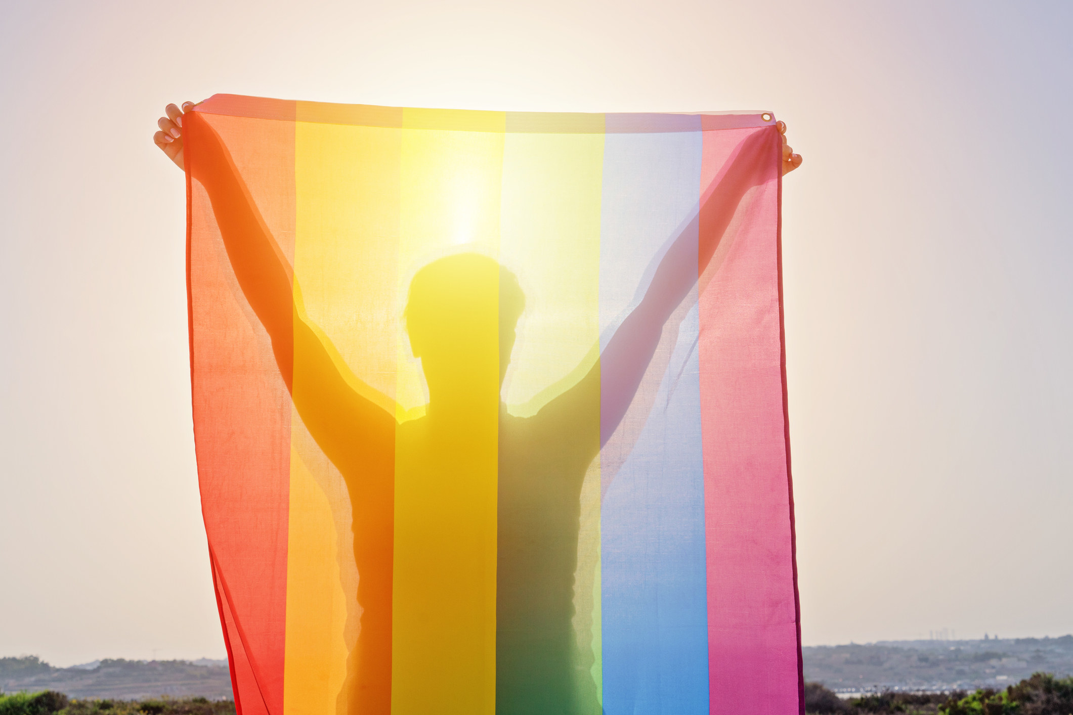 Young woman holding raised hands waving LGBT rainbow flag against sky