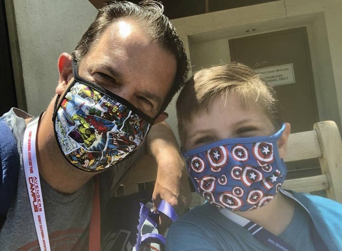 A father and son lean close wearing matching Marvel face masks
