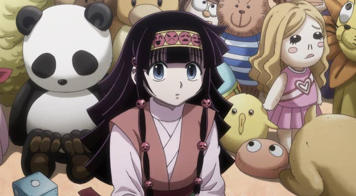Alluka surrounded by a wall of stuffed toys.