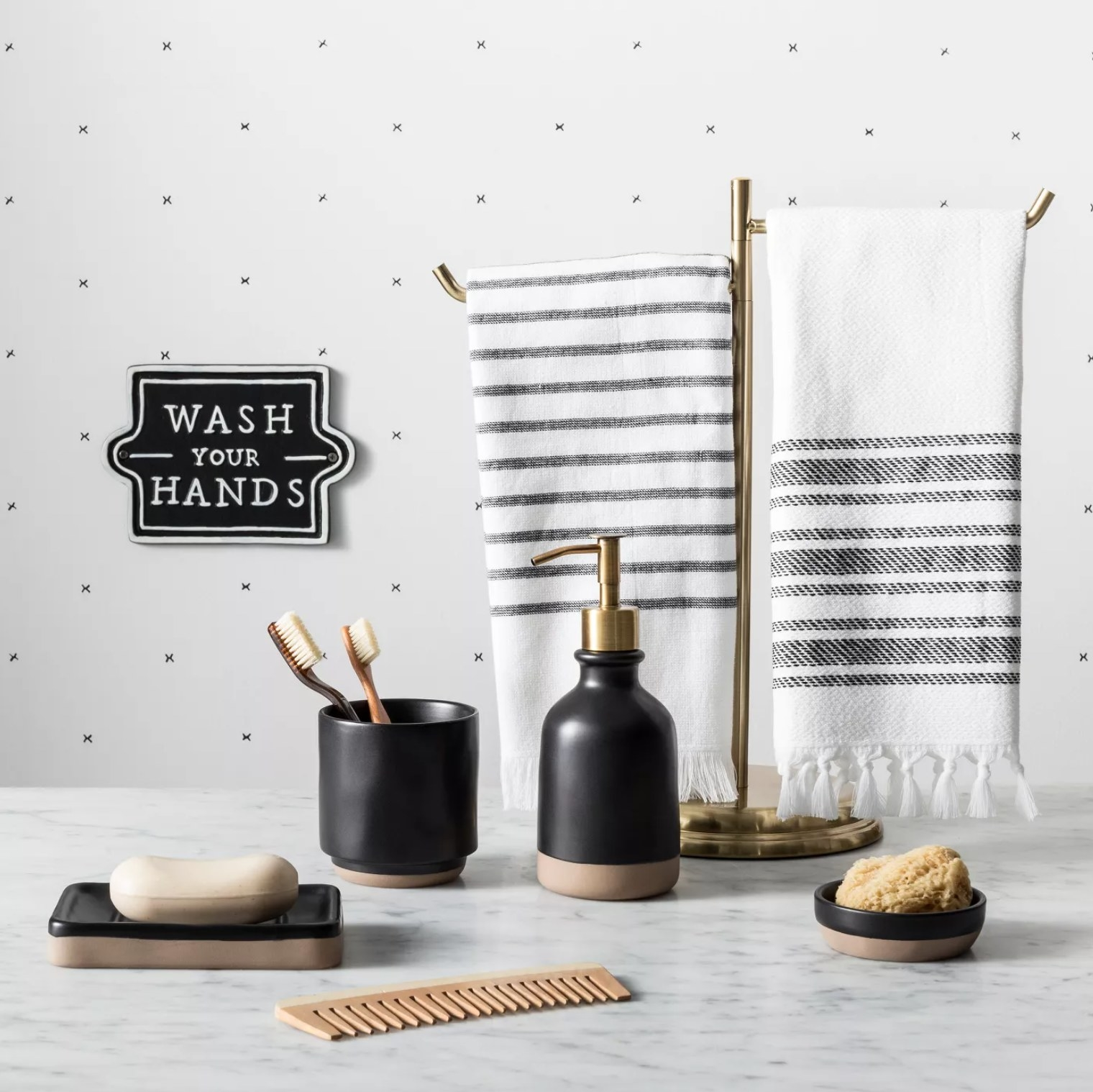 the black and white sign hanging on a wall next to towels and other bathroom accessories