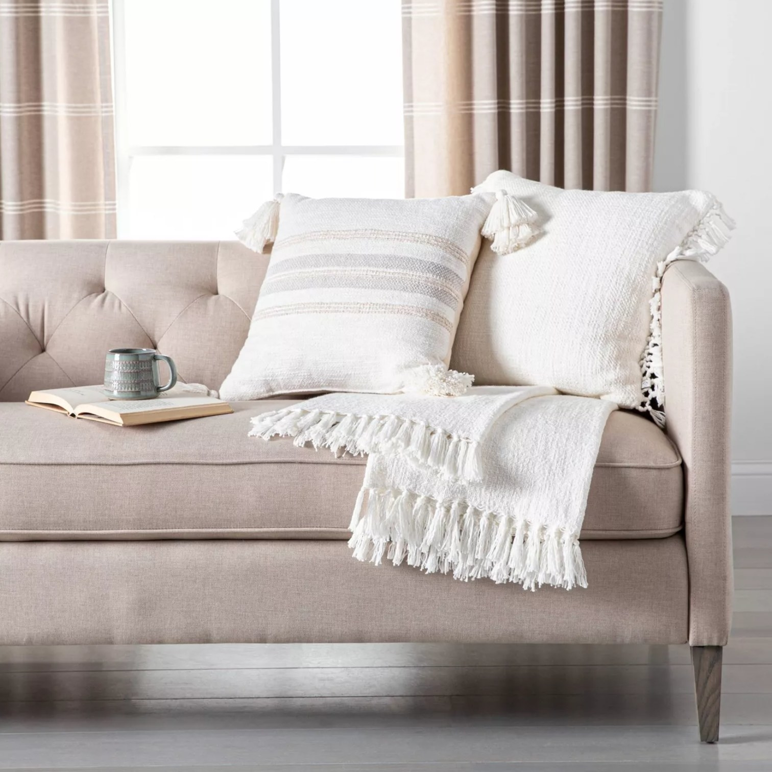 the white blanket on a couch with a pillow and an open book