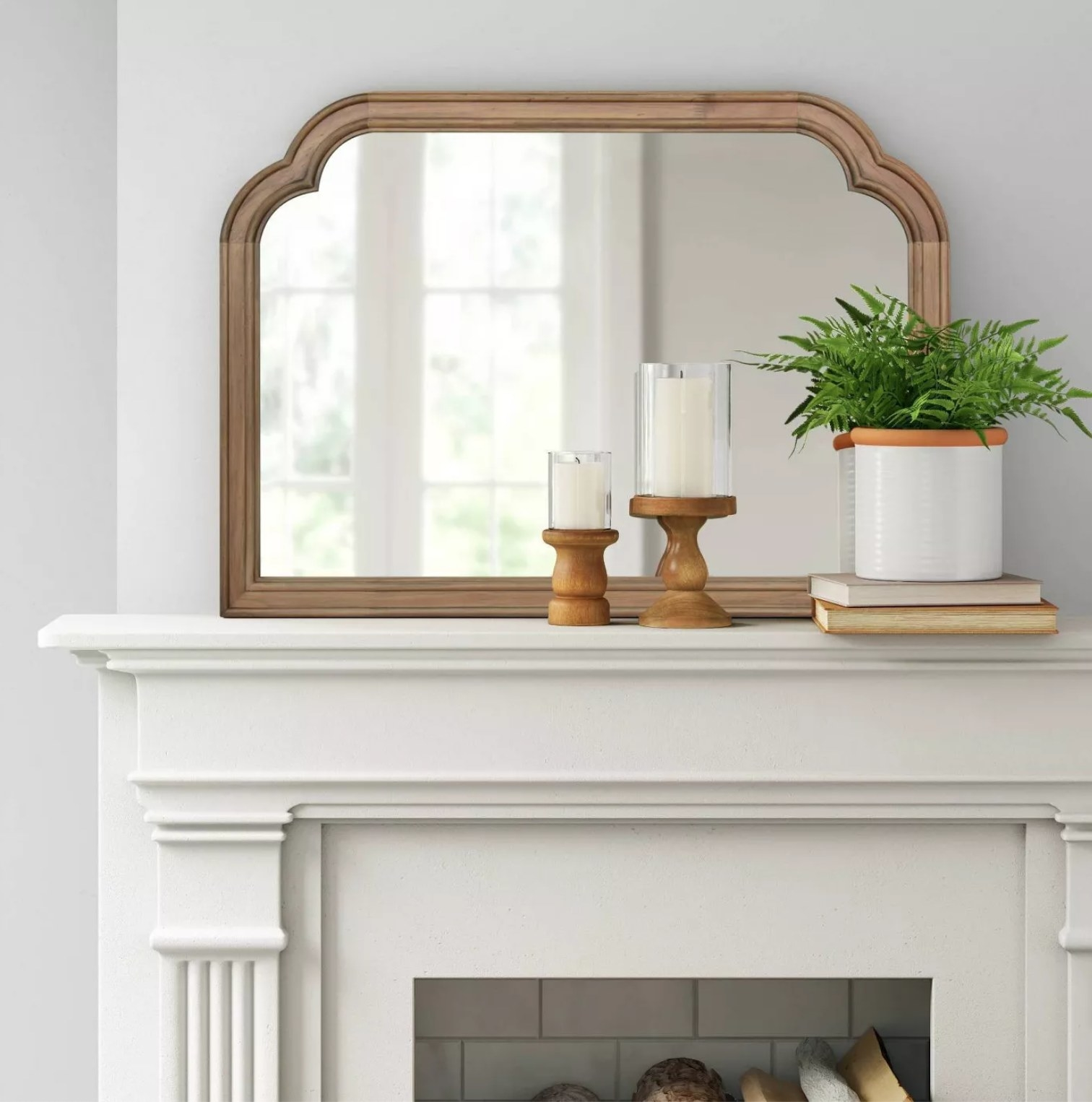 the mirror on a mantle with candles and a plant placed in front of it