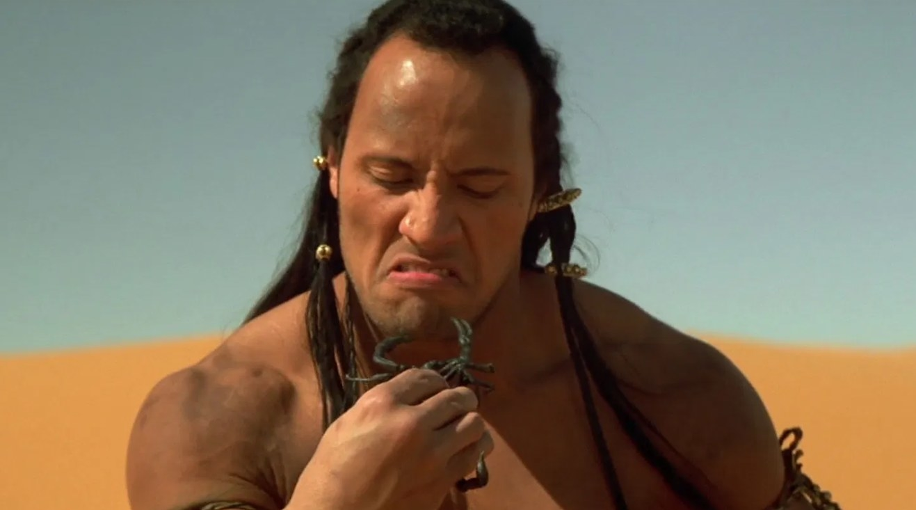The Scorpion King screwing up his face while looking at the scorpion he's holding in his hand