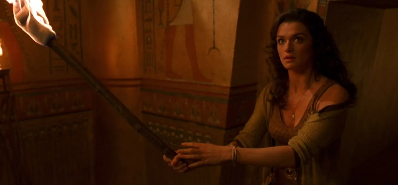 Evie stands in a chamber with hieroglyphics on the walls and holds a fire torch