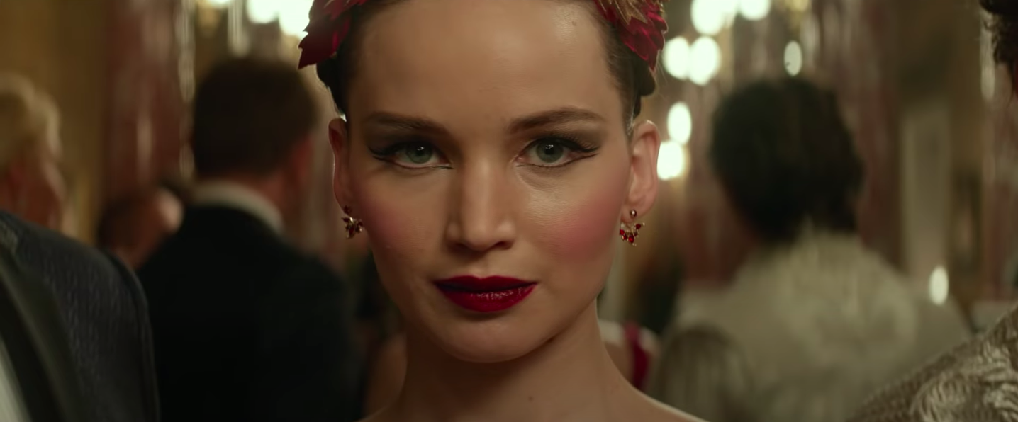 """Dominika Egorova smiling in a small, stilted way in """"Red Sparrow"""""""