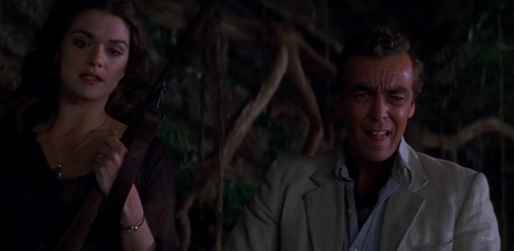 Evie and Jonathan stand next to each other in a jungle; Evie holds a gun