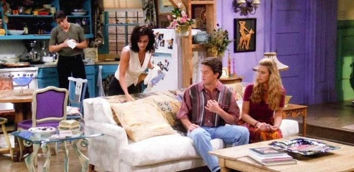 Joey and Monica stand in the kitchen of Monica's apartment while Chandler and Phoebe sit on the couch in Friends