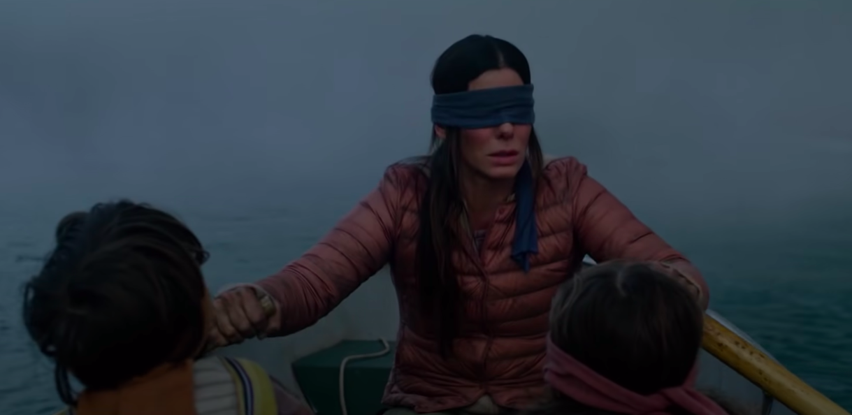 """Malorie rowing a boat that her children are also in in """"Bird Box"""""""
