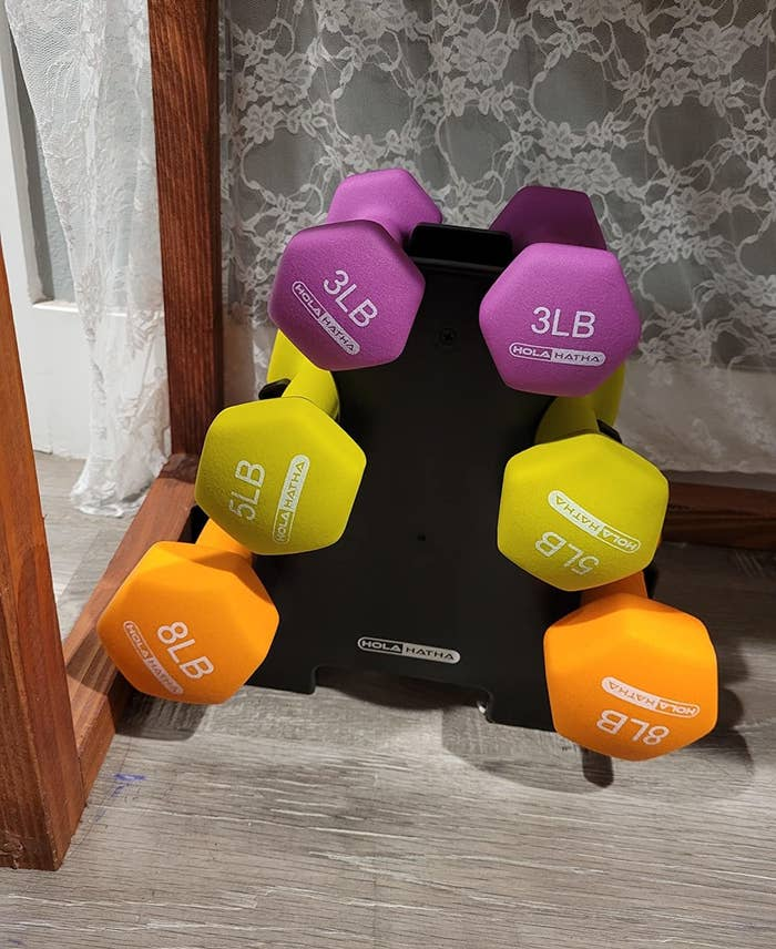 a reviewer photo of the dumbbells on their stand