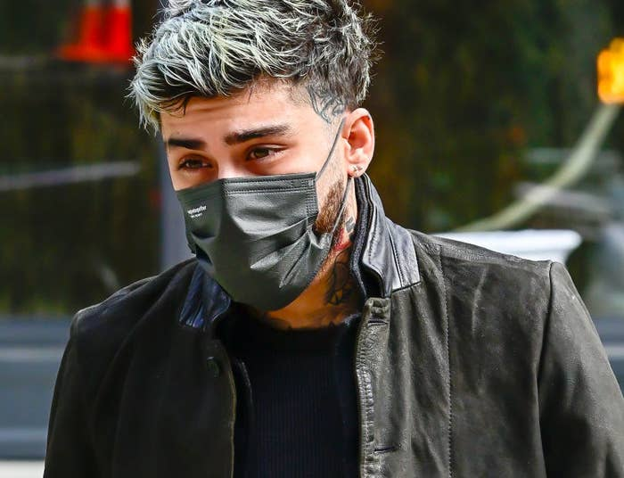 Zayn walking outside with a face mask on his face