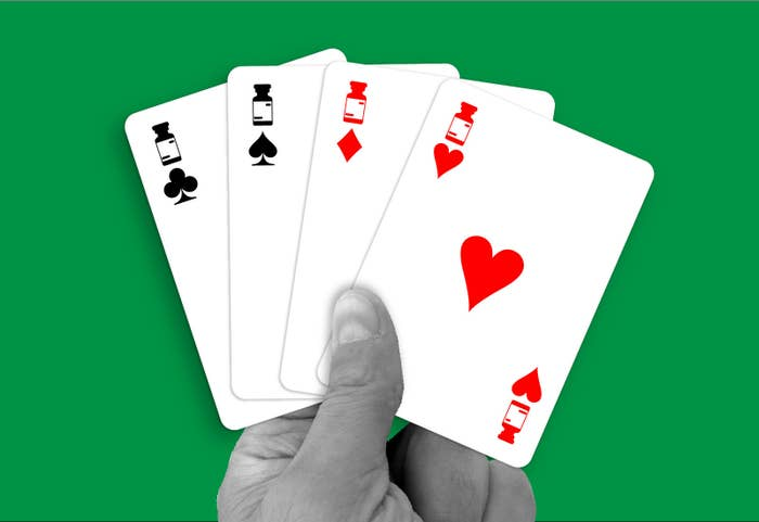 A hand holds four cards of different suits, each with images of a medication container