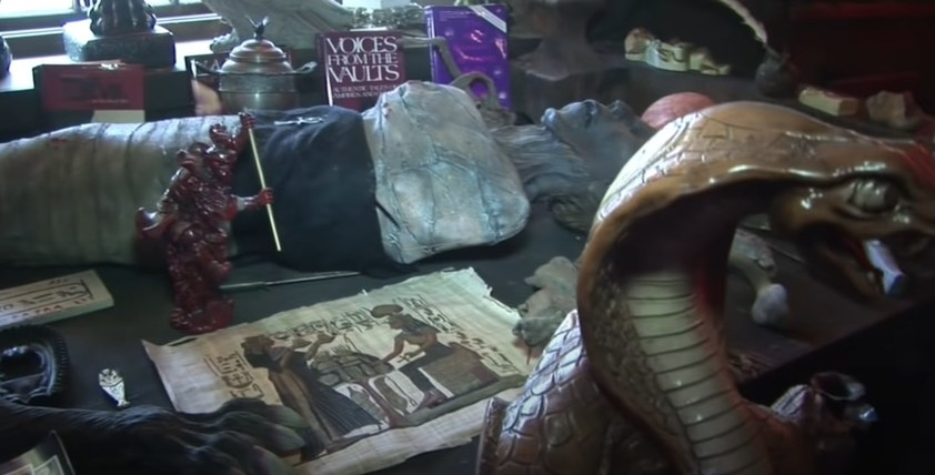 Table of artifacts like a snake statue, mummy, and claw