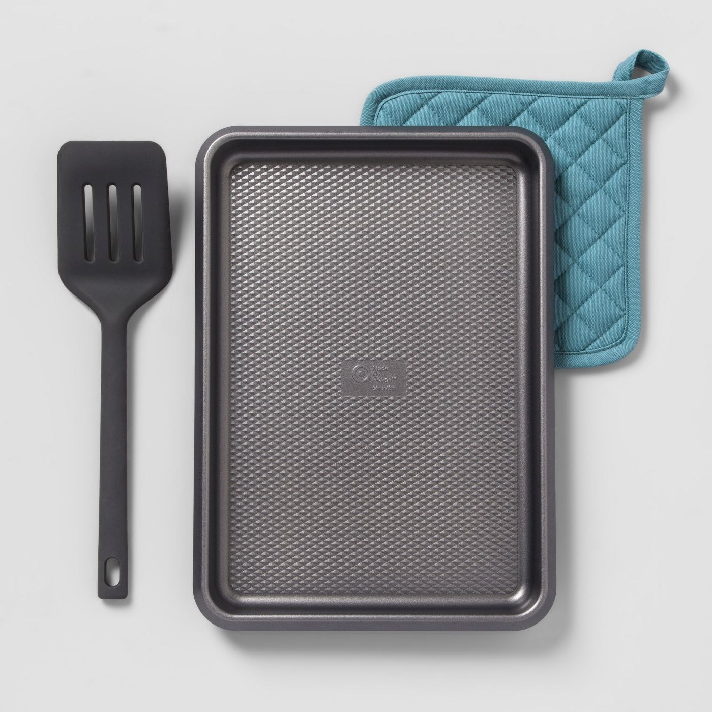 A cookie sheet with spatula and rag