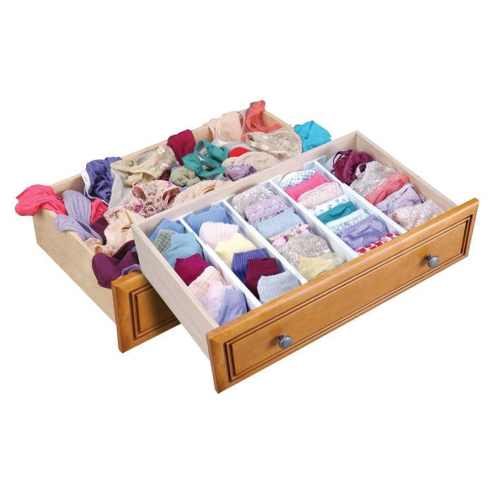 A drawer organizer with colorful clothing inside of it