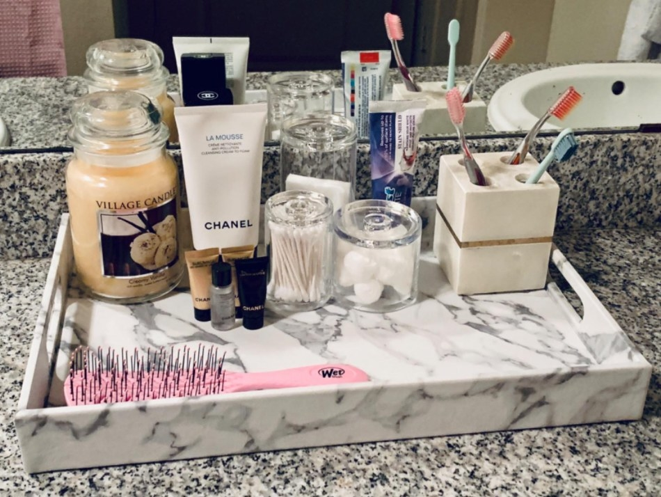 reviewer photo of the tray in their bathroom with skincare products and toiletries