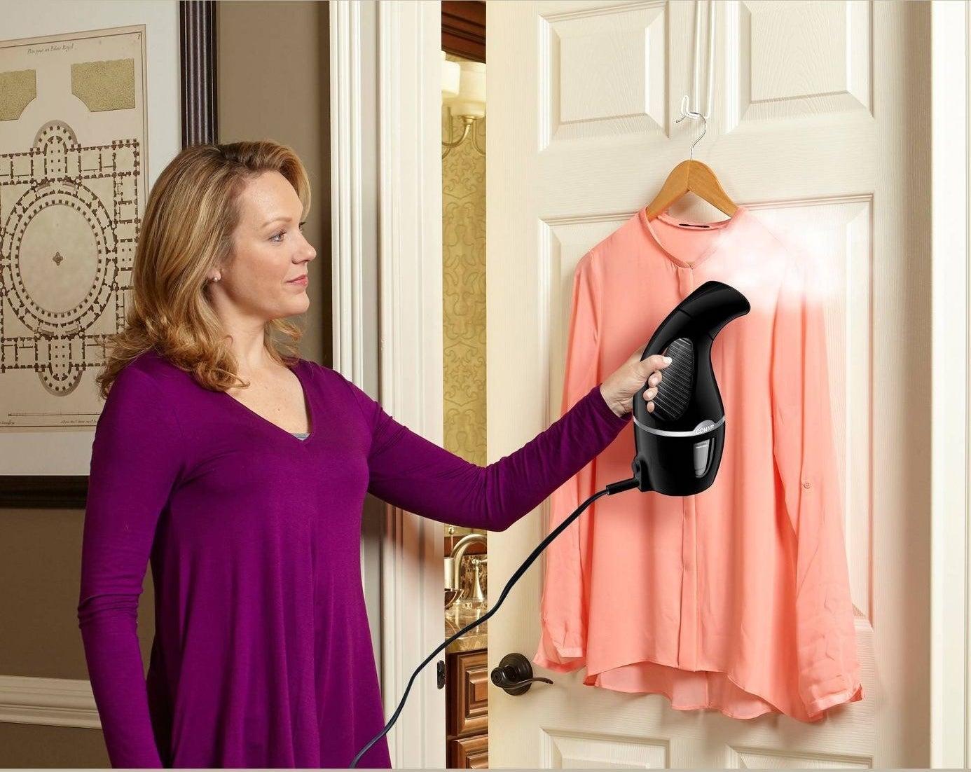Model using black steamer on coral shirt