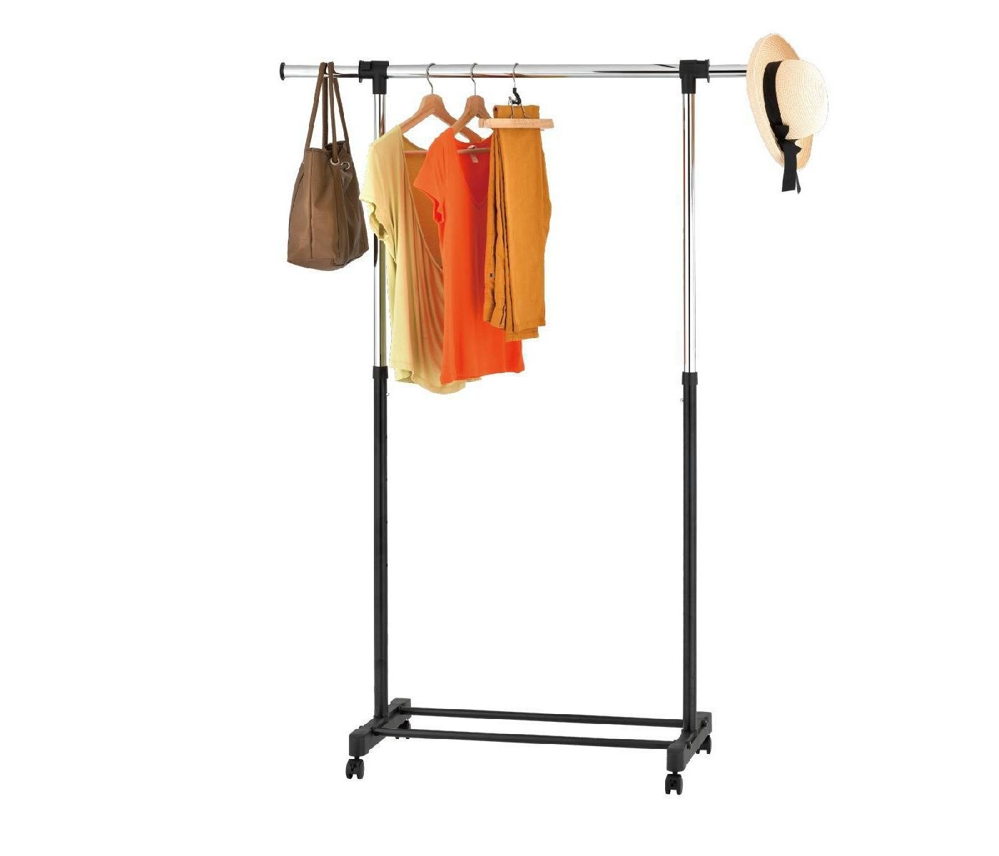 A single rod black garment rack with warm colored clothing on it