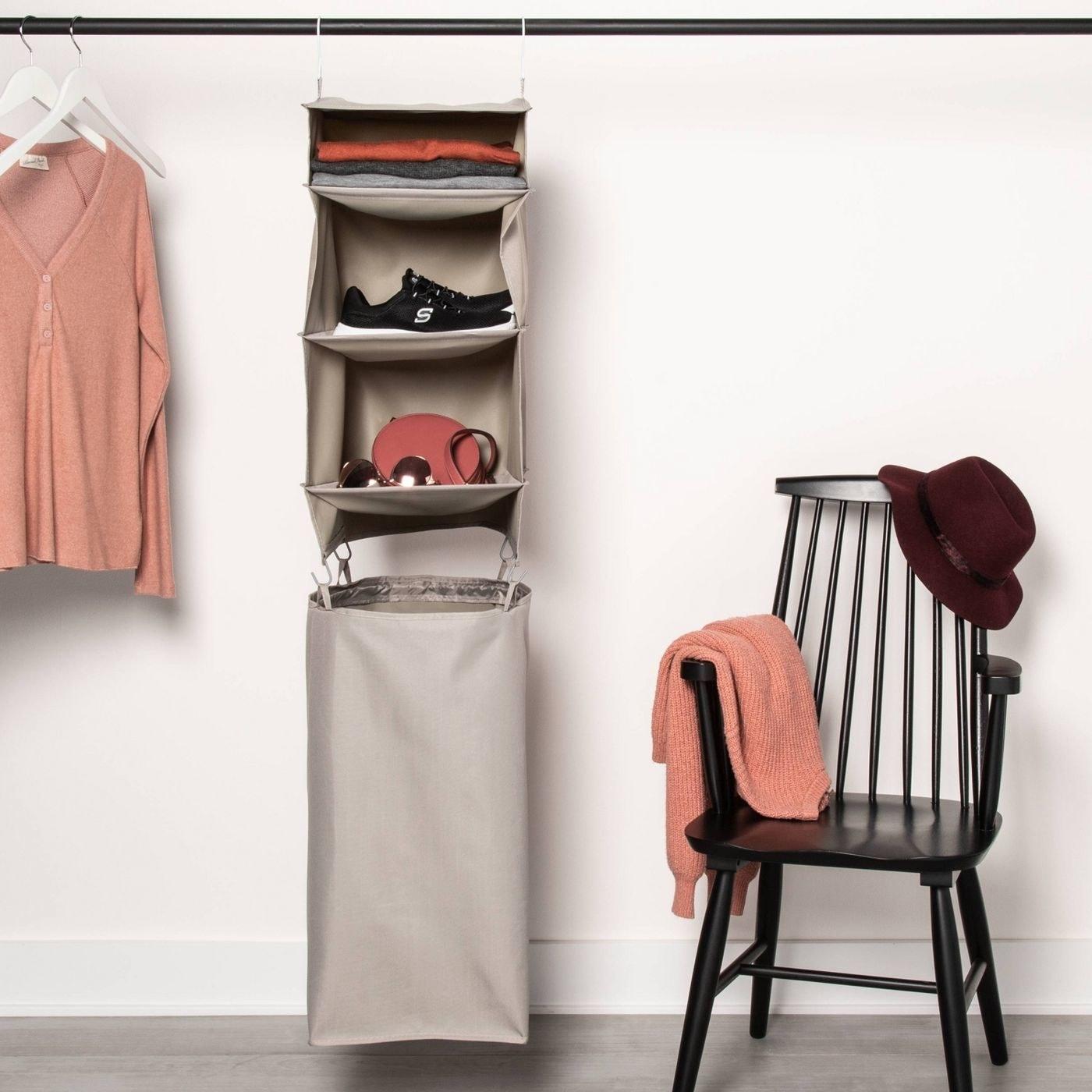 A tan 3-shelf closet organizer with a hamper