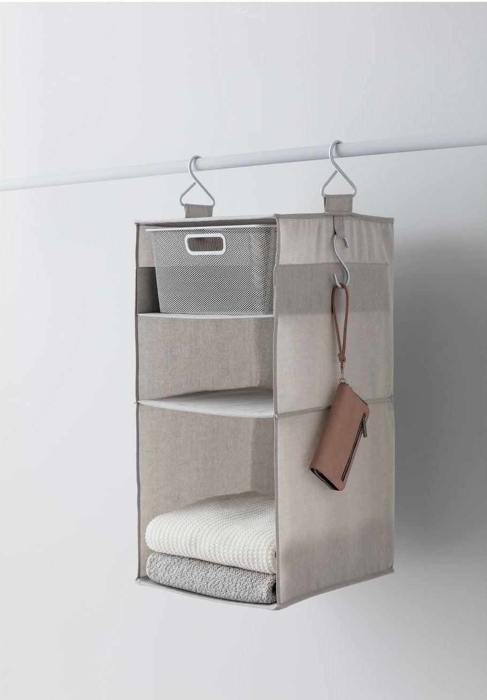 A neutral three-shelf unit in a closet
