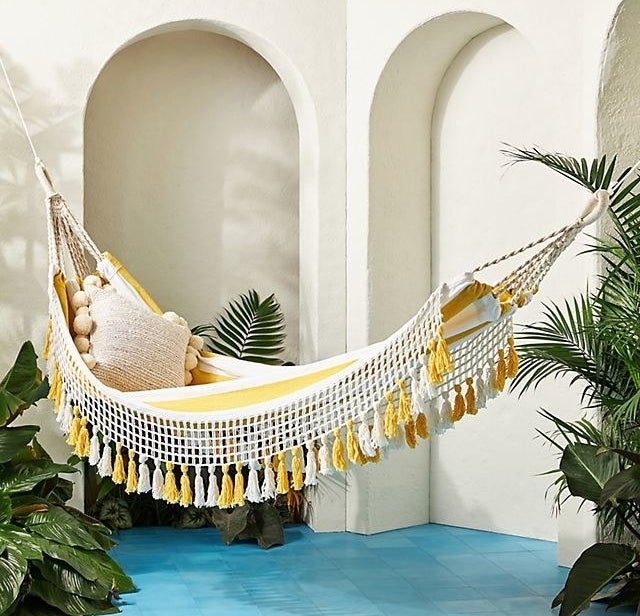 A yellow and white striped hammock with macrame and tassel details