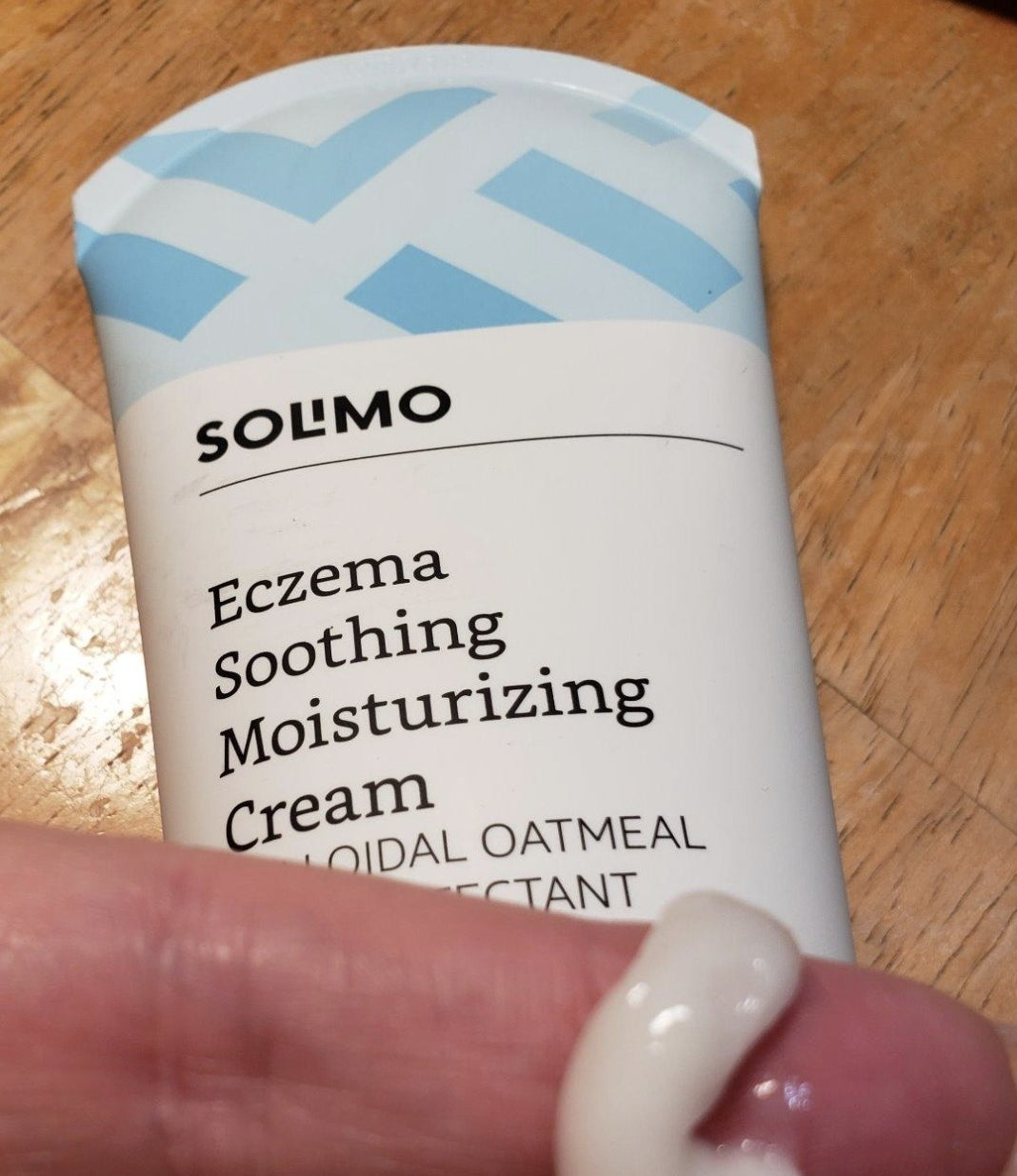 reviewer showing tube of cream as well as a small sample on their finger showing texture/consistency