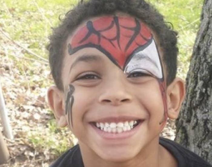 A smiling little boy wears Spider-Man face paint