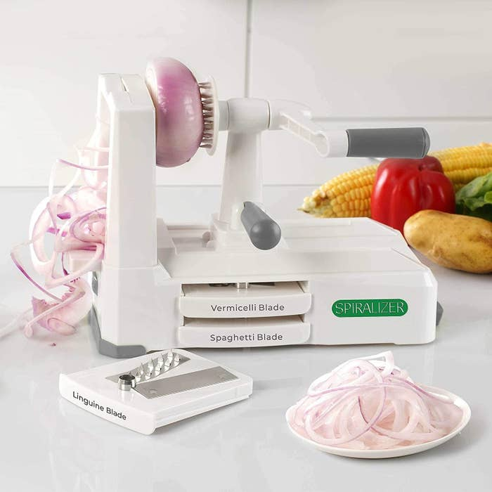 vegetable spiralizer with a crank, with an onion being spiralized