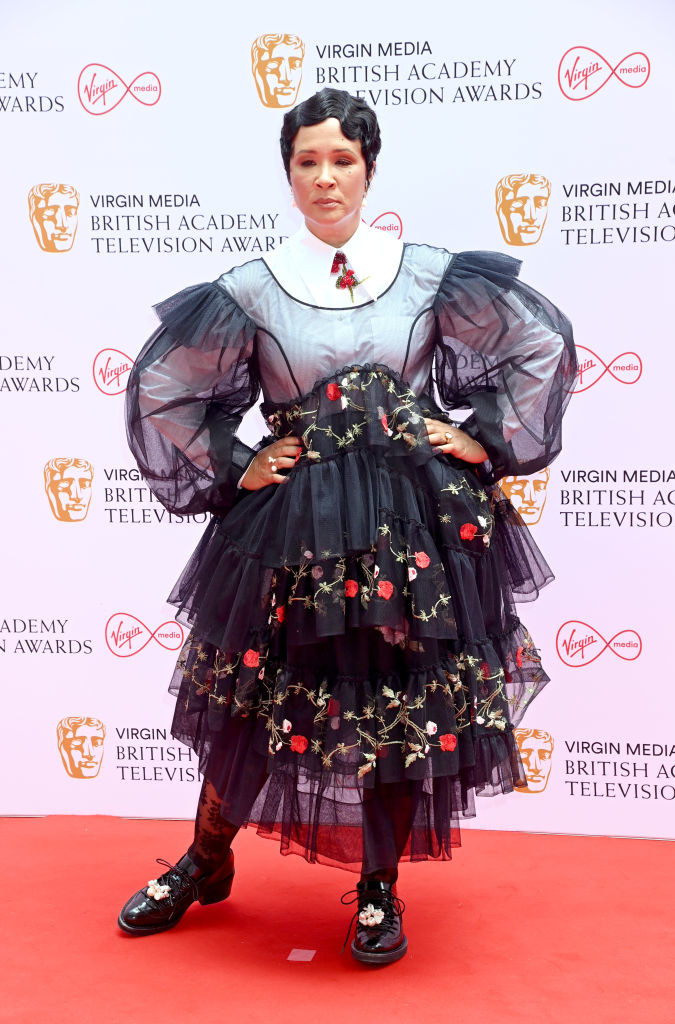Golda Rosheuvel attends the Virgin Media British Academy Television Awards 2021 in a multi-layered print and lace dress with lacy tights and a blouse underneath