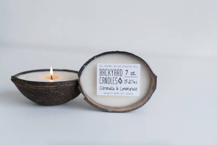 A lit candle in the coconut candle is next to a coconut candle still wrapped and with its packaging on