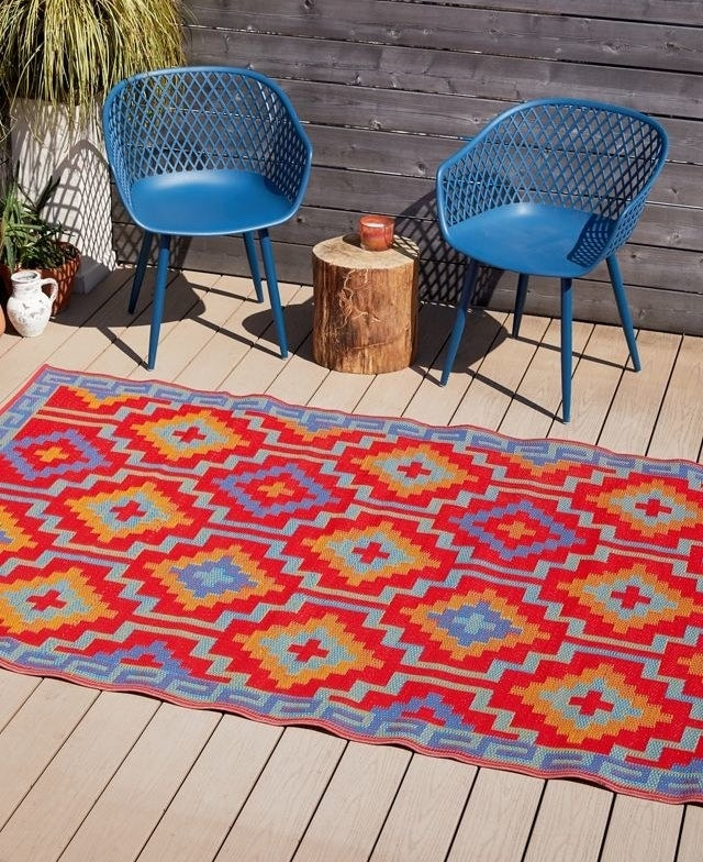 The red and blue rug is displayed outside next to some patio chairs