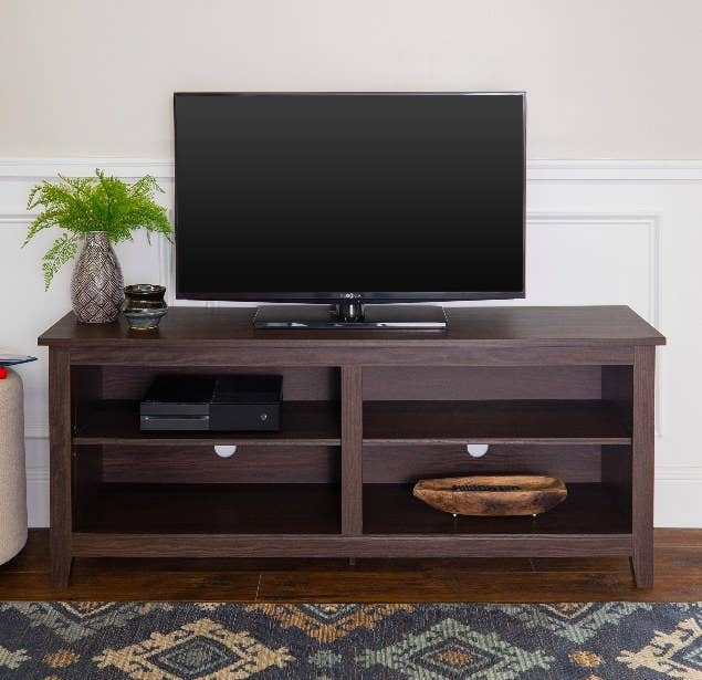 a dark wood entertainment stand with a tv on it