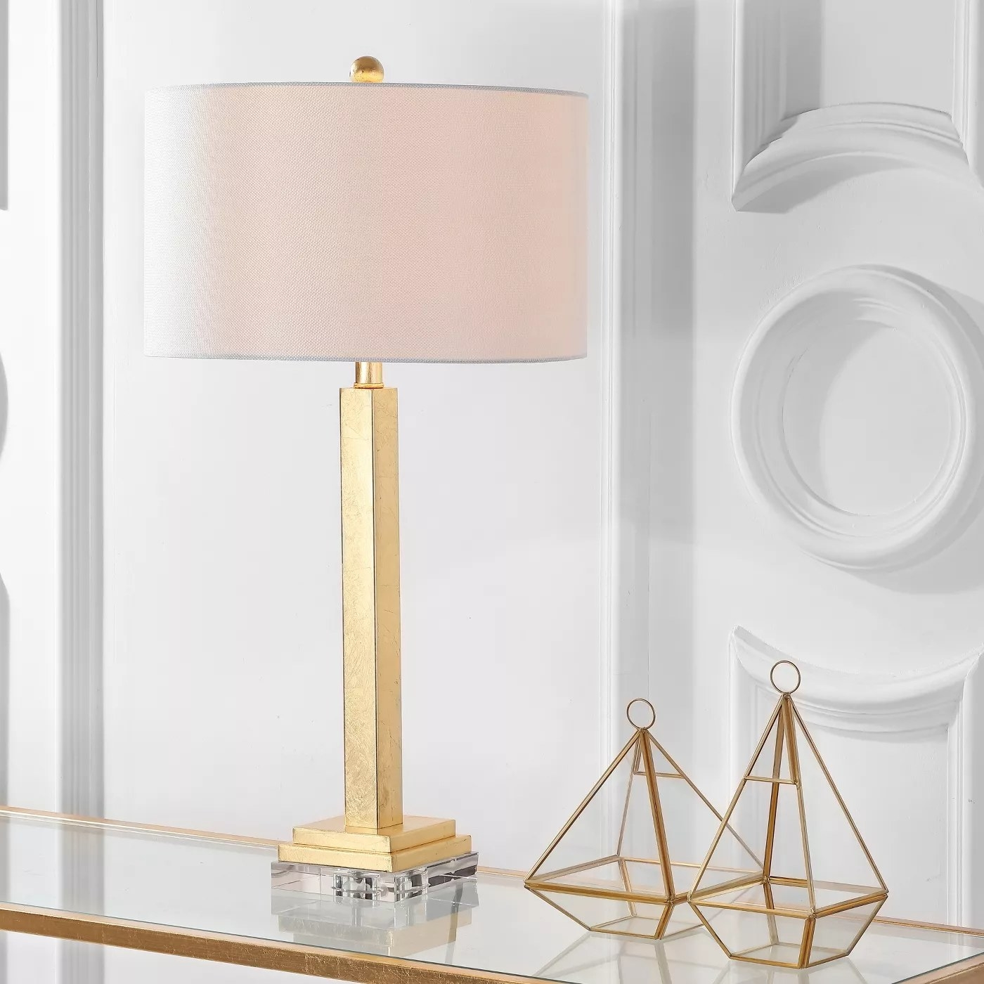 The gold lamp with a white shade and a crystal base