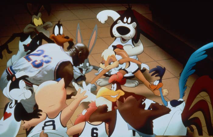 """On set of the 1996 """"Space Jam"""" film, Wile E Coyote, Daffy Duck, Michael Jordan, Bugs Bunny, Lola Bunny, the Road Runner, Foghorn Leghorn, Tazmanian Devil, Yosemite Sam, Porky Pig, and Pepe Le Pew put their hands together in cheer"""