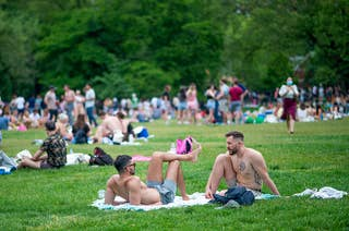 Two shirtless men lounge in the forefront with a huge crowd of people behind them in a park