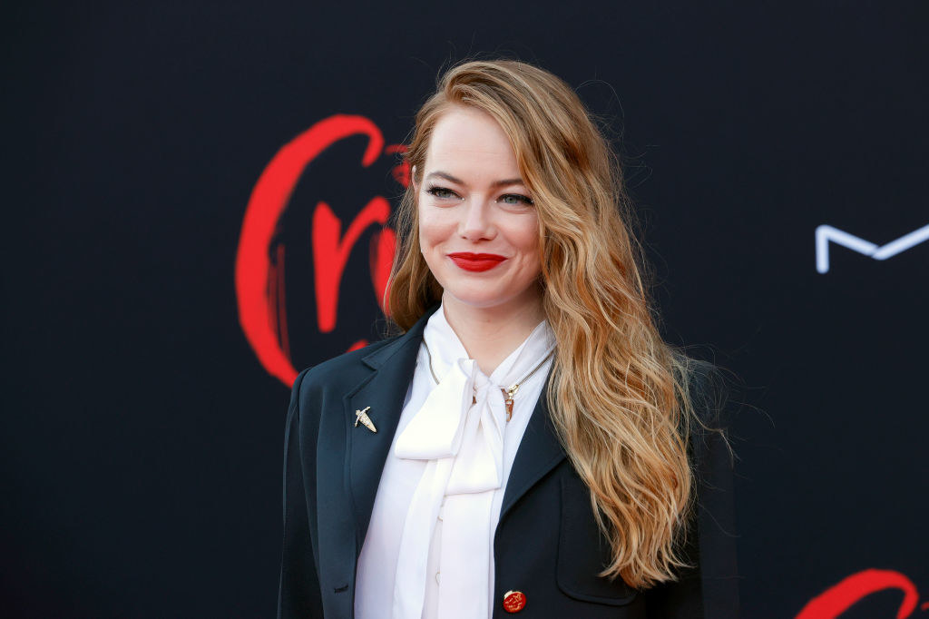 """Emma Stone, wearing a black blazer over a white button up shirt, smiles while posing on the red carpet for her movie """"Cruella."""""""