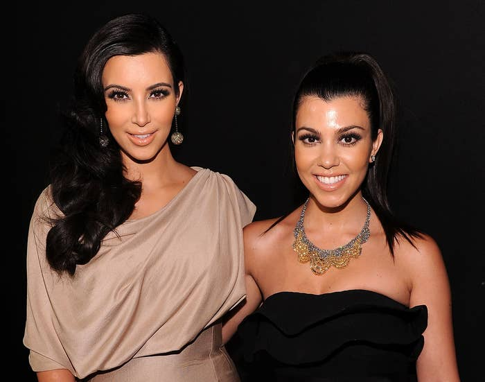 Kim and Kourtney smile while attending an event