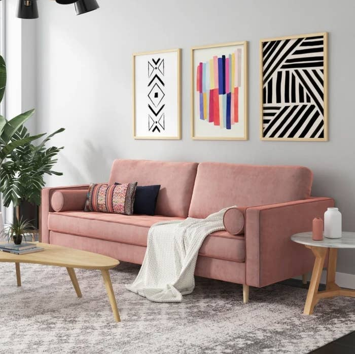 A blush pink, velvet sofa displayed in a living room with accent pillows and a throw blanket on top
